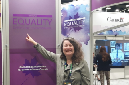 "Anne Gloger, Principal of The Centre for Connected Communities, smiles while pointing to a sign reading ""Gender. Equality Everyone Everywhere"""