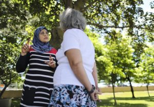 Miyadah Subrati speaking to a resident inside a park