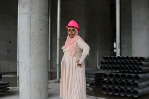 Sureya Ibrahim wearing a pink dress and pink hard hat at a construction site